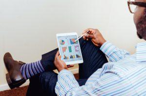 man sits, leg crossed, viewing analytics on tablet