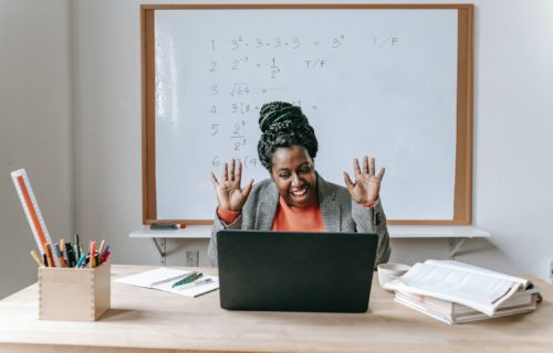 Woman sitting in front of computer waving hands, smiling, with whiteboard behind her