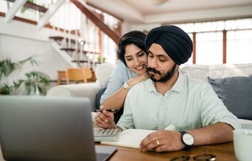 Serious young Sikh man with hugging wife counting on calculator at home